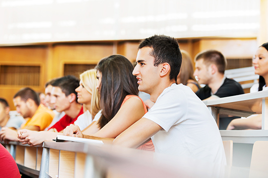 Large group of college students sitting in the university amphitheatre. The focus is on the male student in white t-shirt.