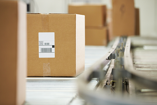 Goods Moving On Conveyor Belt In Distribution Warehouse